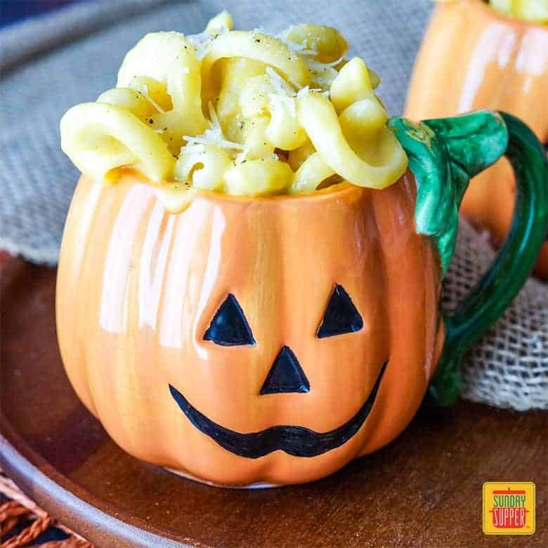 Pumpkin Mac and Cheese in a mug shaped like a jack-o-lantern