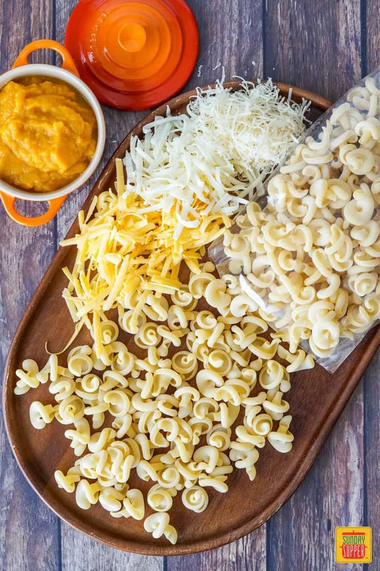 Pasta, cheese, and pumpkin puree for Pumpkin Mac and Cheese on a wooden serving board