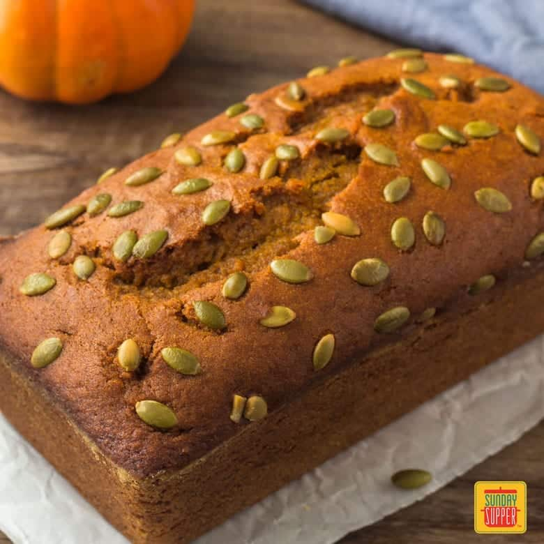 A whole loaf of starbucks pumpkin bread with pumpkin seeds on top