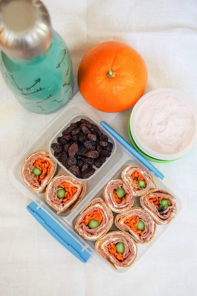 Kid Friendly Lunch Ideas: Pinwheel sandwiches of deli roast beef, cheese spread, carrots and asparagus rolled into a tortilla and served with raisins and yogurt dip in a lunch box