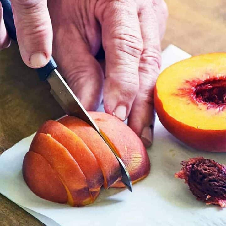 Cutting a peach into slices on a white surface next to half a peach and a peach pit