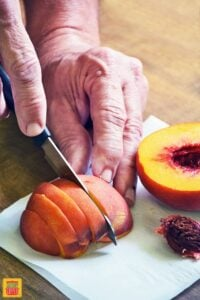 How to cut peaches: slicing the peach into slices on a white cutting board
