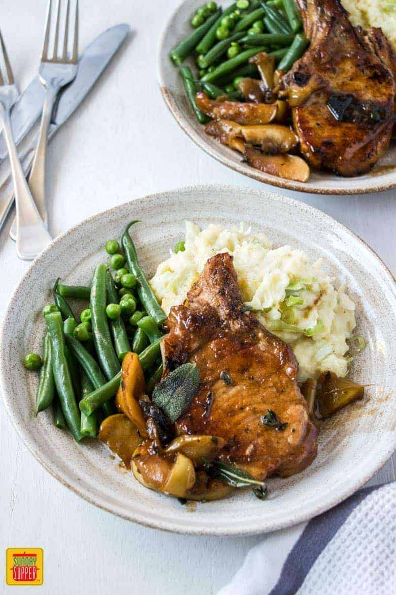 Baked Apple Pork Chops served on white plates with mashed potatoes and green beans