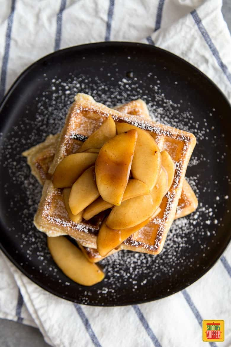 Sauteed Apples over waffles with powdered sugar on top on a black plate