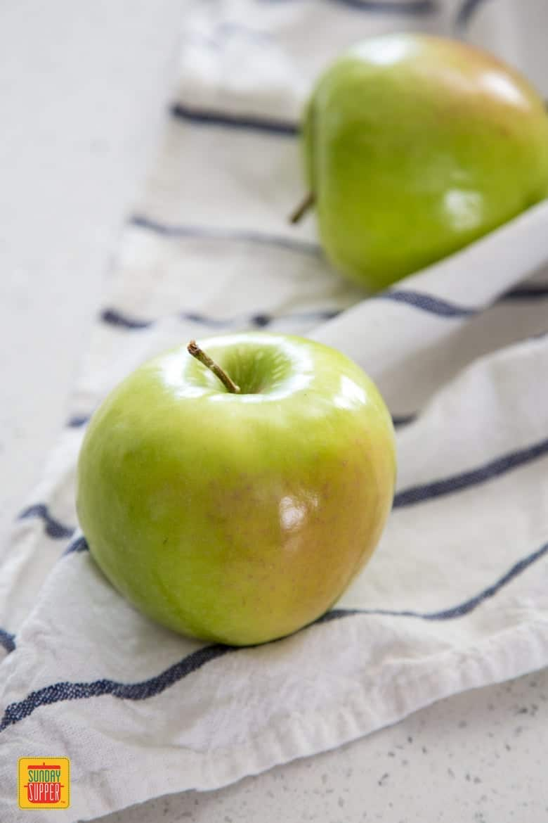 Granny Smith apples for Sauteed Apples sitting on a white and blue towel