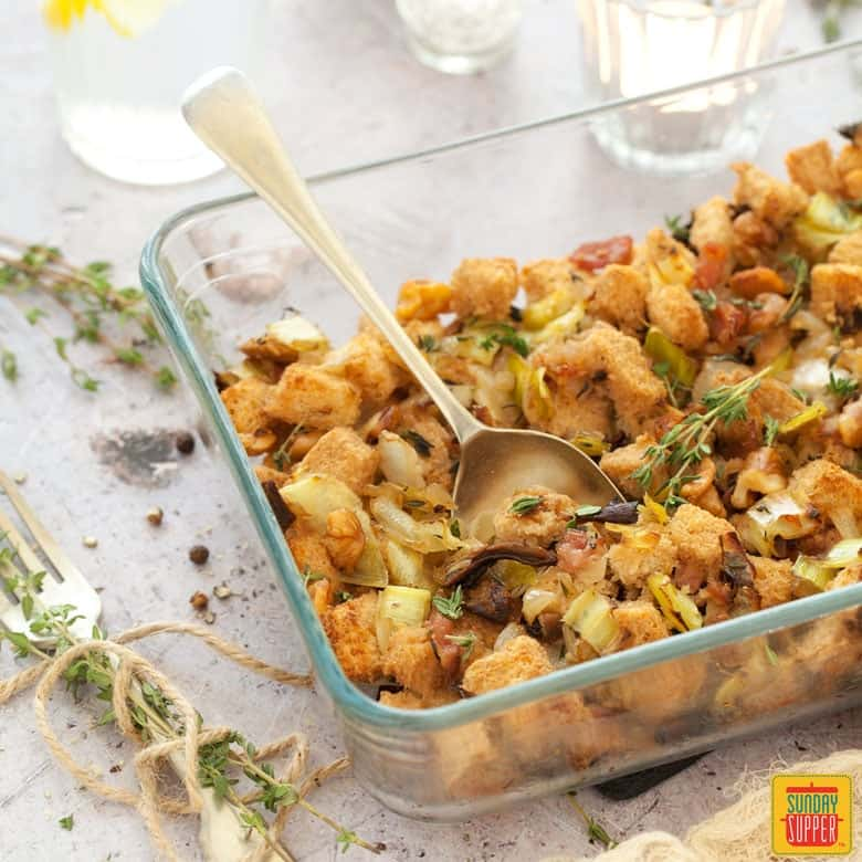 gluten free stuffing in a casserole dish with a serving spoon