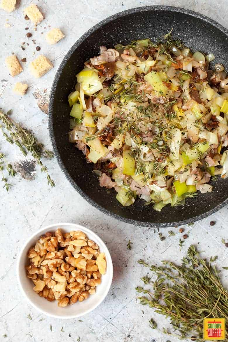 Mixing ingredients for gluten free stuffing recipe in a skillet