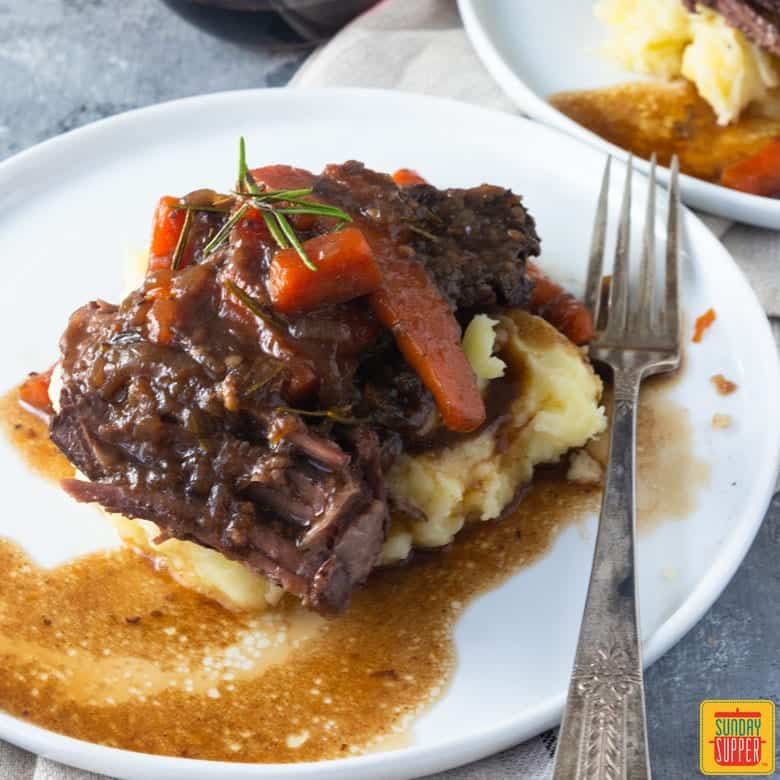 dutch oven pot roast on a bed of mash potatoes on white plate