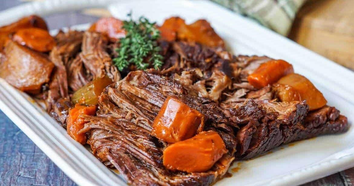 Beef chuck roast on a platter with root vegetables