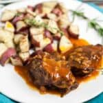 Instant pot pot roast on a white plate with potatoes and herbs
