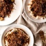 Two bowls of Mississippi Pot Roast served over mashed potatoes