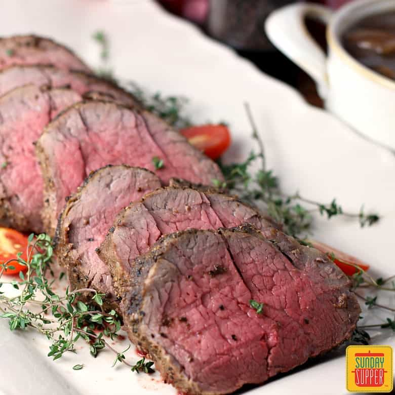 Whole beef tenderloin sliced on a white platter with fresh herbs