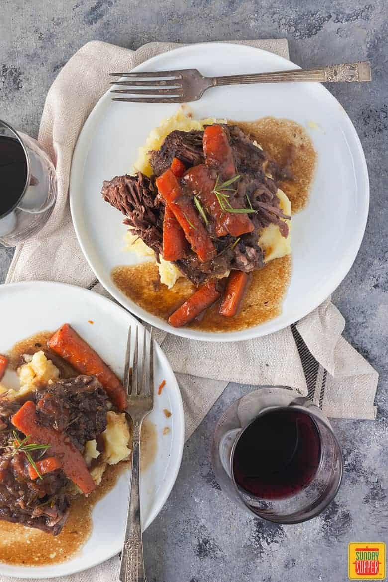 dutch oven pot roast on two white plates with red wine