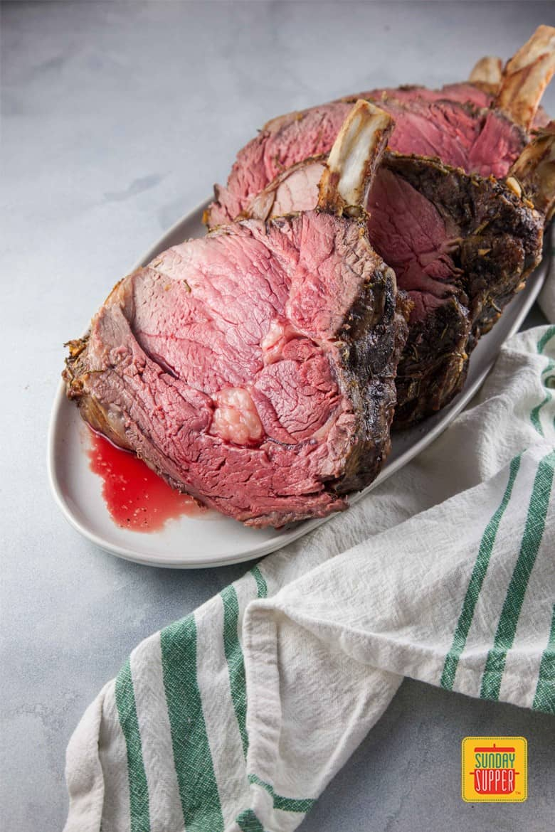 Standing Rib Roast Recipe perfectly cooked to mid-rare sliced on a white serving platter