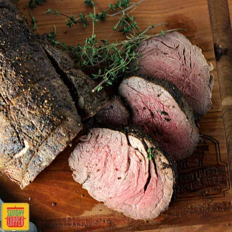 Whole beef tenderloin sliced on a cutting board with fresh sprigs of herbs