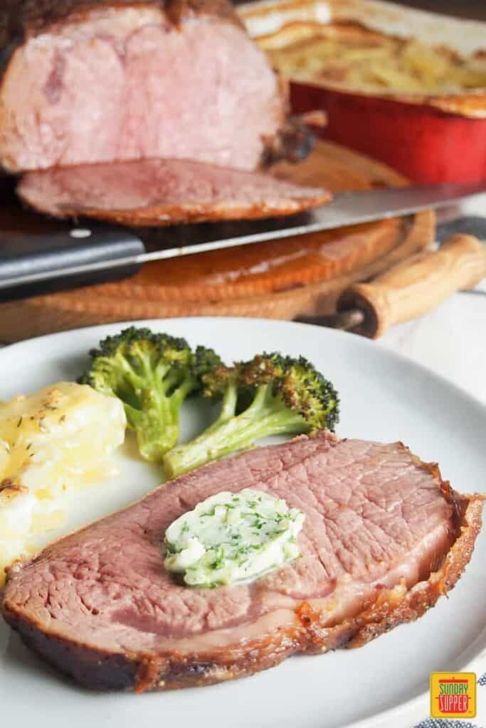 Slice of boneless prime rib roast on a plate with herb butter and vegetables