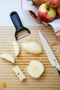 Slices of apples on a wooden cutting board next to a peeler and knife