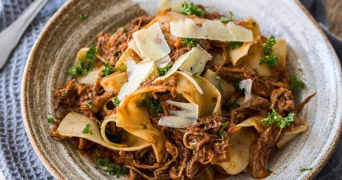 Slow Cooker Beef Ragu is a full flavored, slow cooked ragu perfect for a cold winters night. Served over thick strands of parpadelle, this is comfort food heaven.