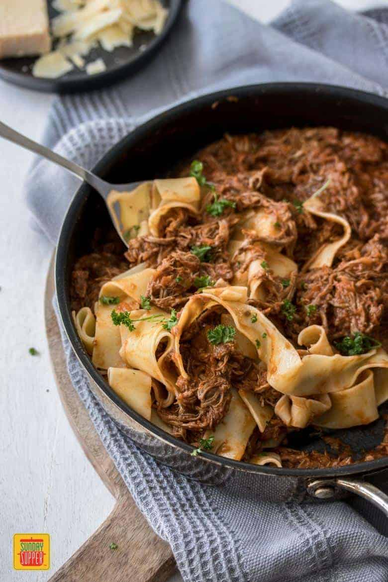 Slow Cooker Beef Ragu with pappardelle pasta being served from a skillet