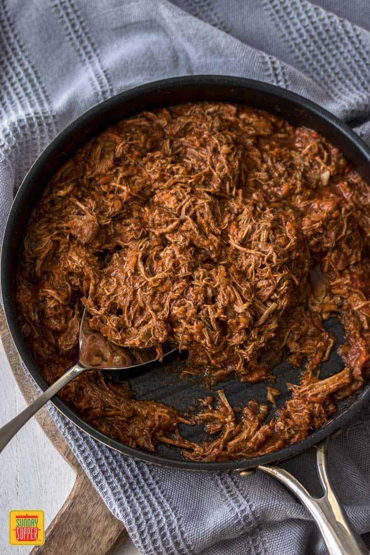Slow Cooker Beef Ragu shredded in a skillet