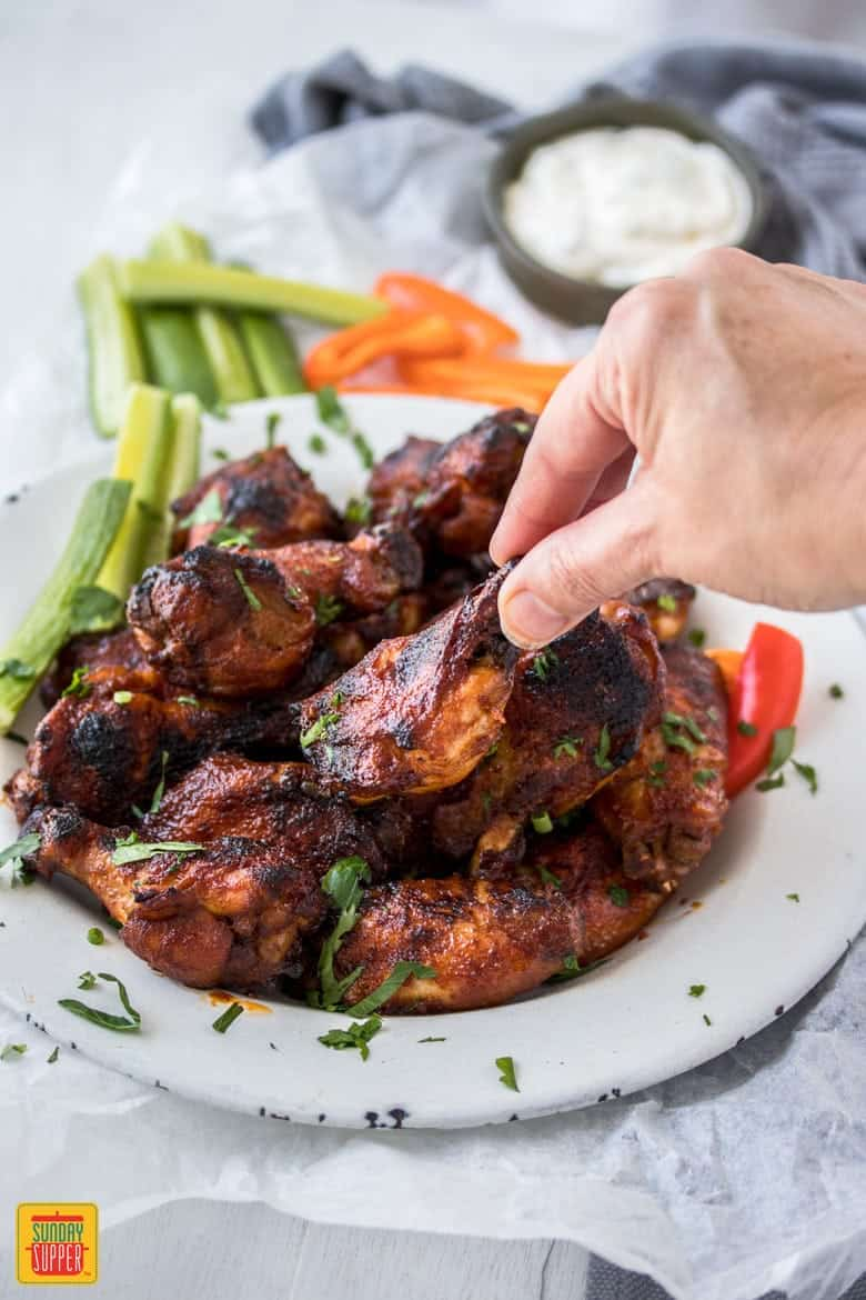 A woman's hand picking up a crispy slow cooker wing to enjoy