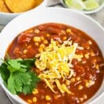 A white bowl of Slow Cooker Vegetarian Chili topped with cheese & cilantro