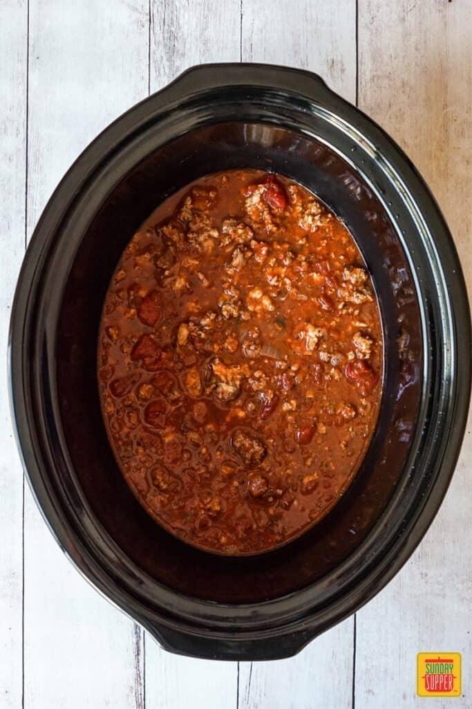 Layering the slow cooker lasagna