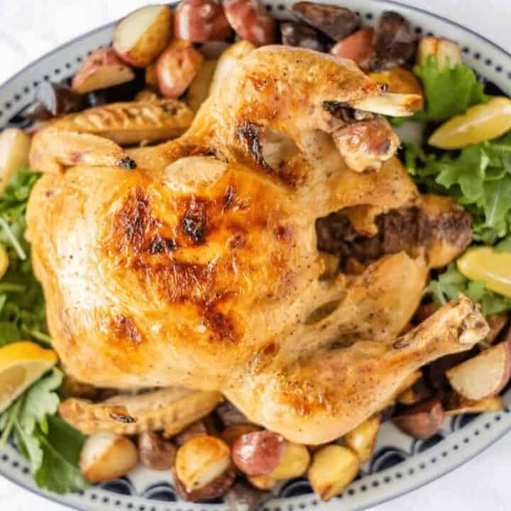 Slow Cooker Whole Chicken on serving tray surrounded by greens, roasted potatoes, and lemon wedges