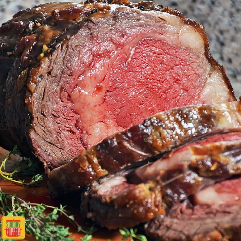 Perfect mid-rare slow roasted prime rib sliced and ready to serve