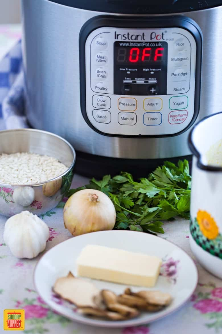 Ingredients for Instant Pot Risotto: parsley, onions, rice, butter, dried porcini mushrooms, broth and garlic sitting in front of the instant pot on the table