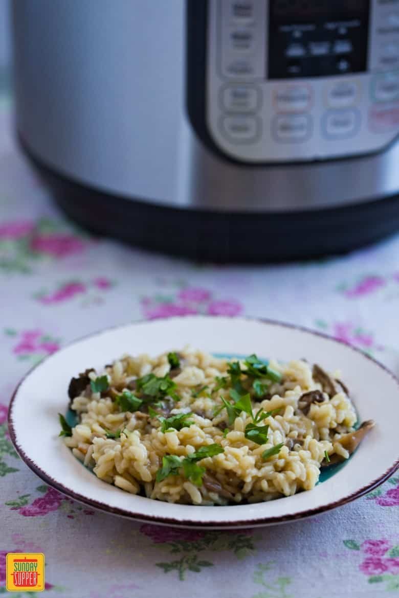 Instant Pot Risotto just prepared and served on a white plate with a brown rim on a floral tablecloth