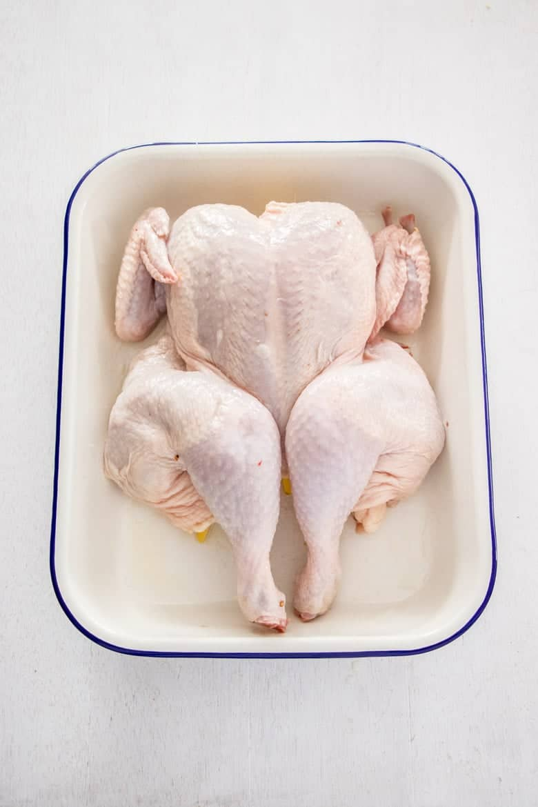 Peri Peri Chicken Recipe - whole chicken placed in roasting pan, ready to be basted