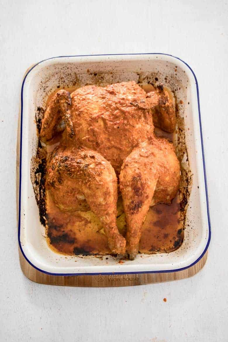 Peri Peri Chicken Recipe - whole roasted peri peri chicken in roasting pan, cooked and ready to begin serving