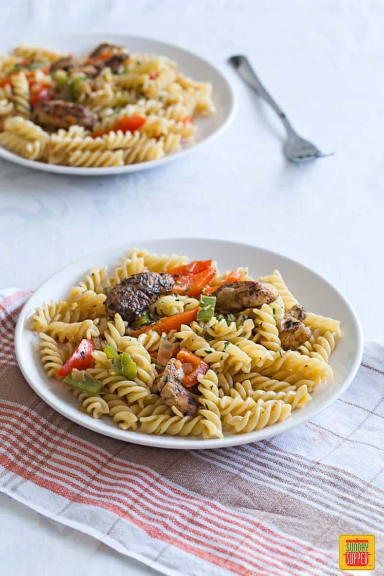 Rasta Pasta for two with jerk chicken and bell peppers, served on white plates, ready to eat