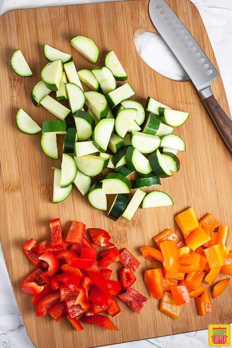 Diced zucchini and red and orange bell peppers on a cutting board, for filling the vegetarian tacos