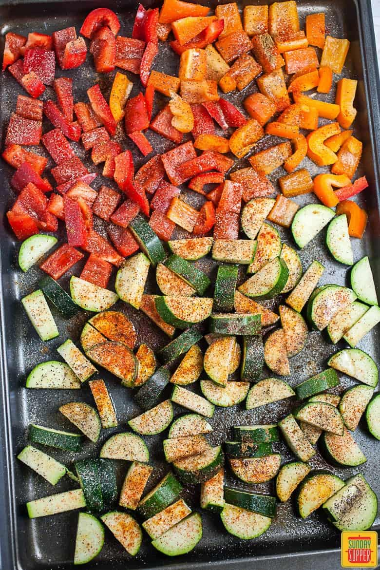 Diced zucchini and bell peppers on a baking sheet, seasoned and ready to roast in the oven for the vegetarian taco recipe for two