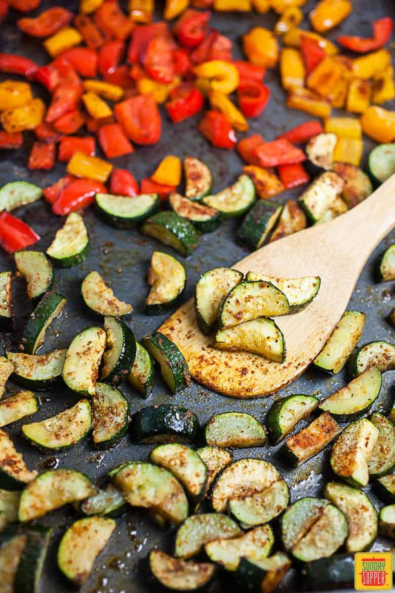 Diced, seasoned, and roasted zucchini and bell peppers on a baking sheet, ready to add to vegetarian tacos