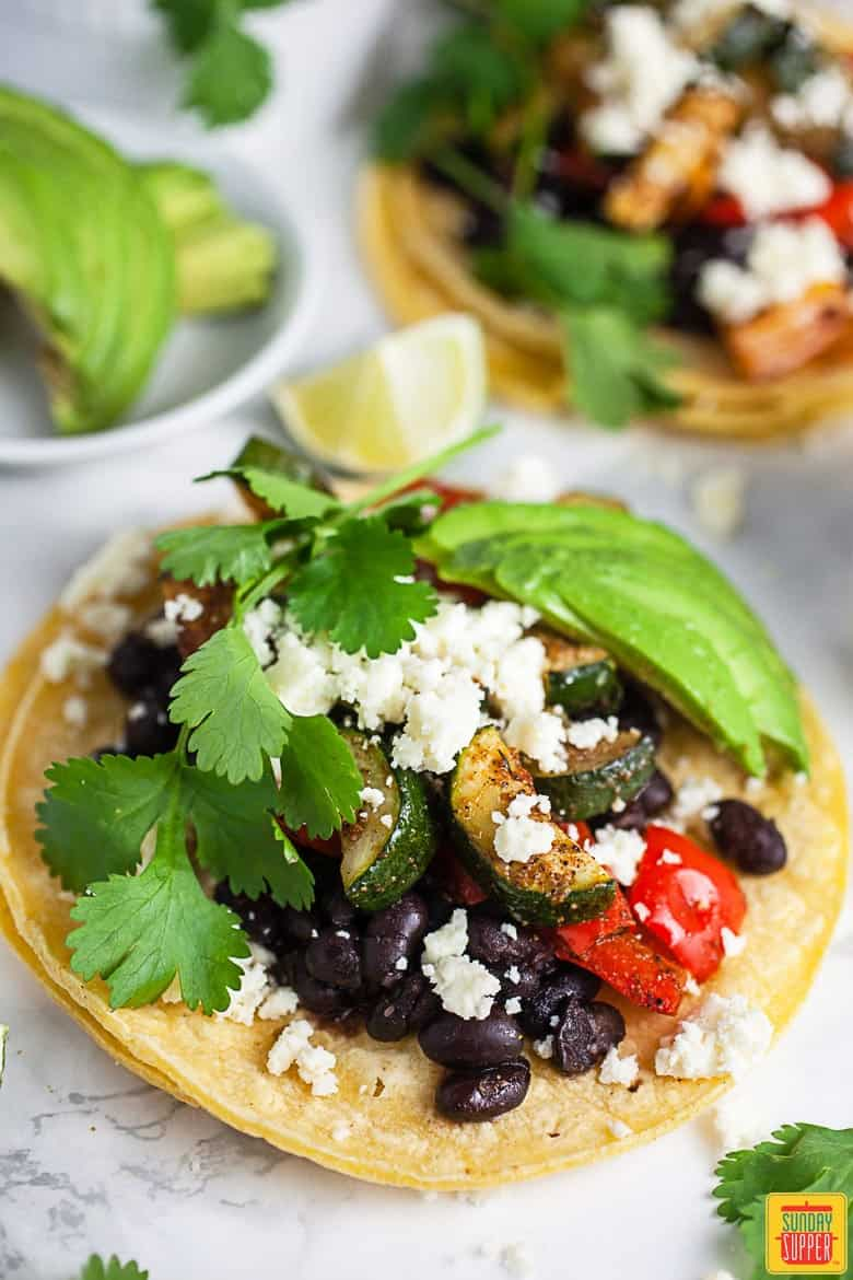 Vegetarian tacos served on corn tortillas with avocado and seasonal vegetables