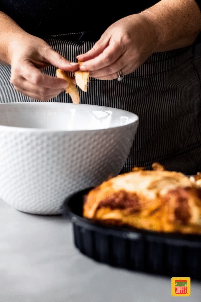 woman shredding a rotisserie chicken into a large white bowl