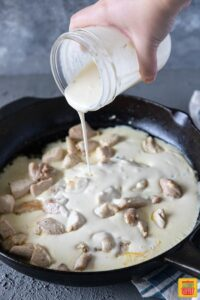 Alfredo Sauce being poured into fettuccine alfredo with chicken