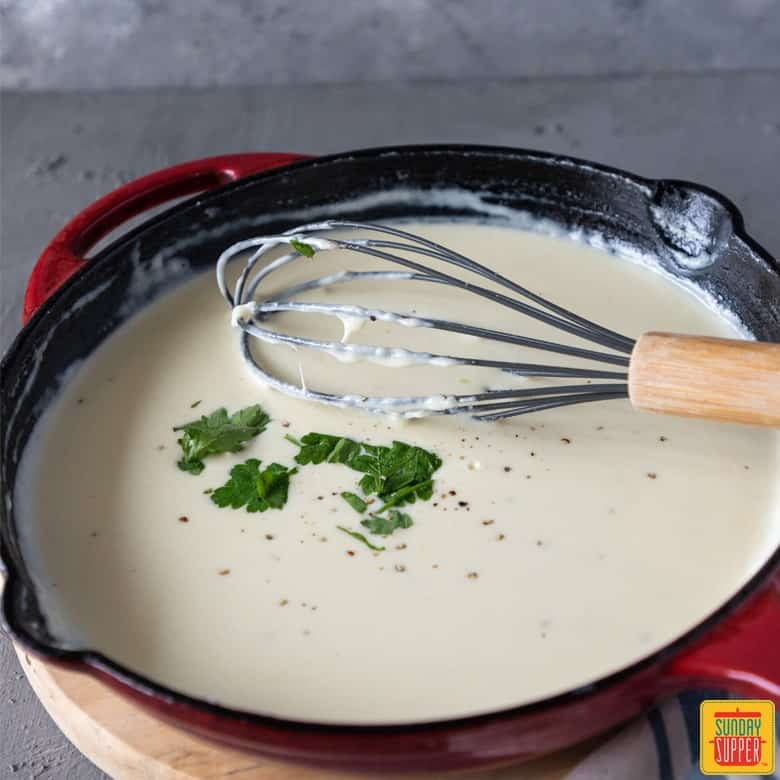 Alfredo sauce in a red skillet over a cutting board, with a whisk, for how to make alfredo sauce