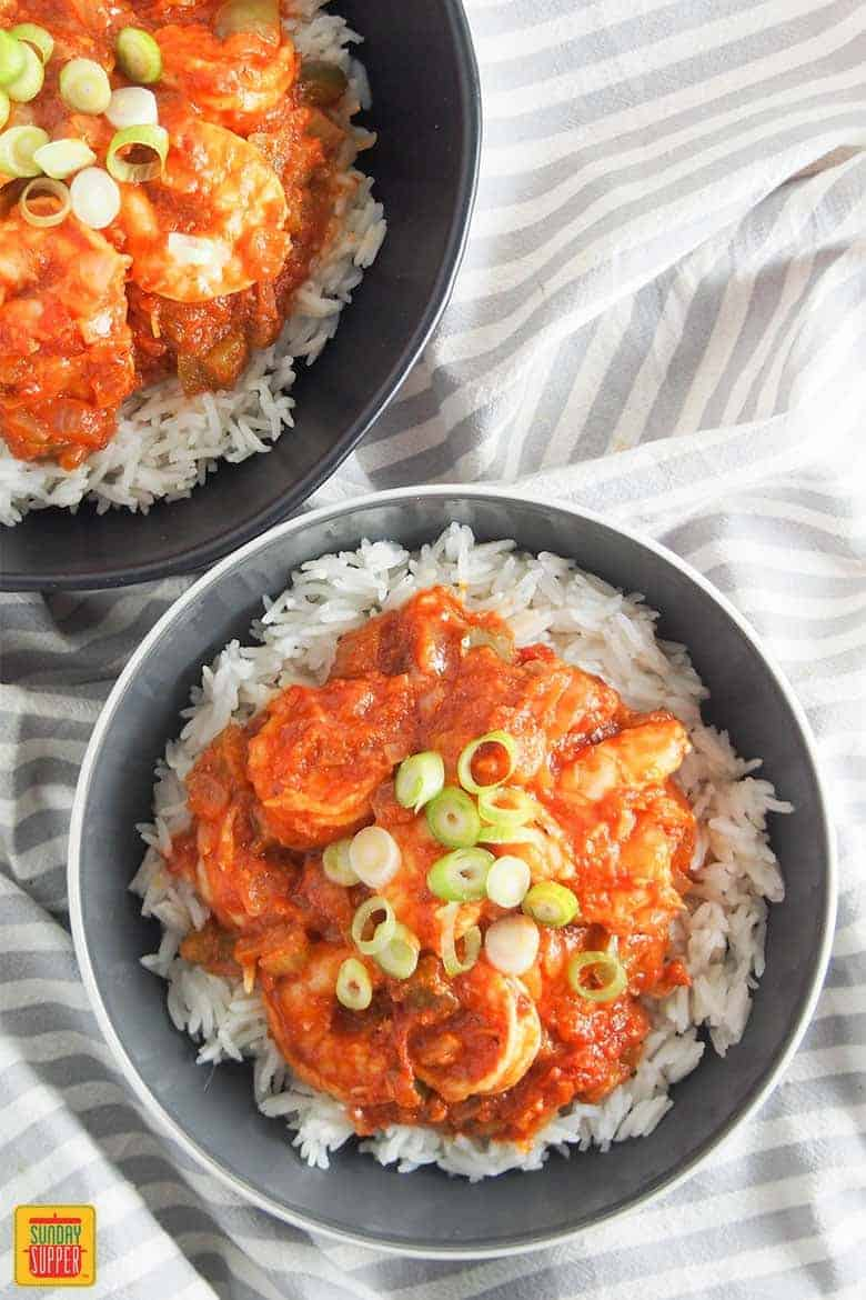shrimp creole recipe for two in a dark gray bowl served over rice topped with green onions