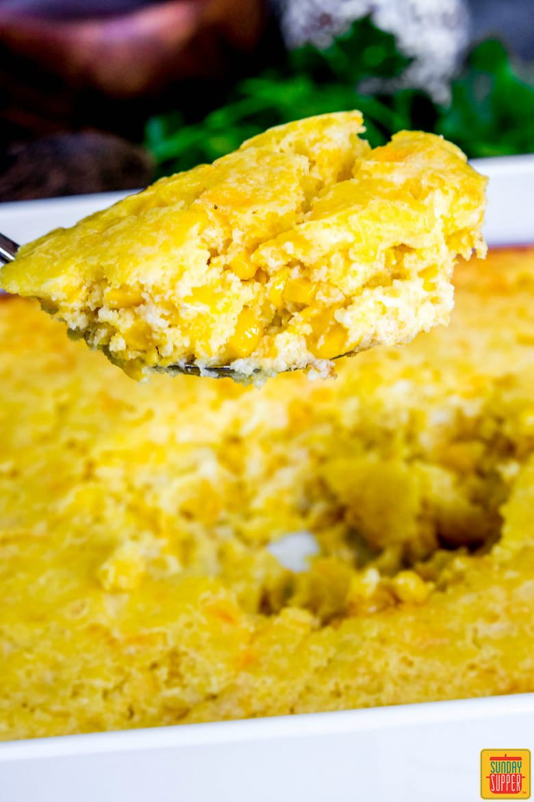 A spoonful of baked creamed corn casserole, ready to eat