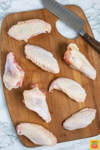 Cut chicken wings for buffalo wings on cutting board with knife