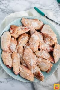 Chicken wings coated with dry ingredients in a bowl