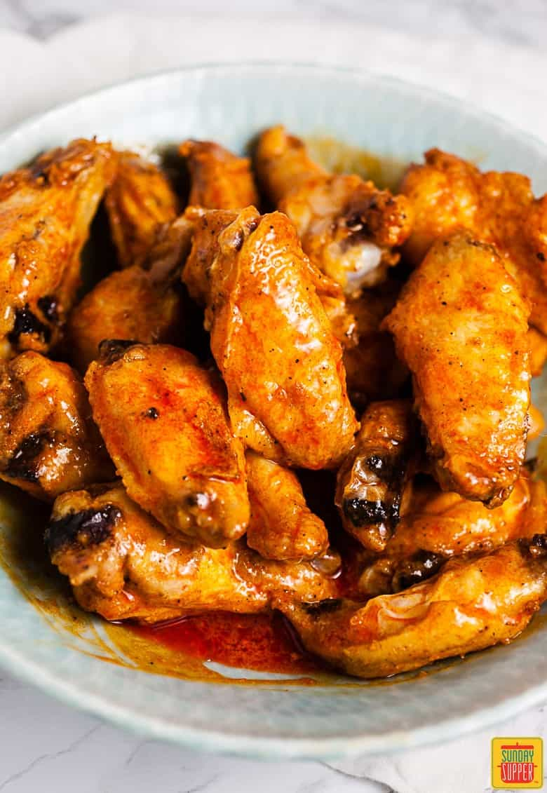 How to Make Buffalo Wings: wings in a bowl, tossed with buffalo sauce