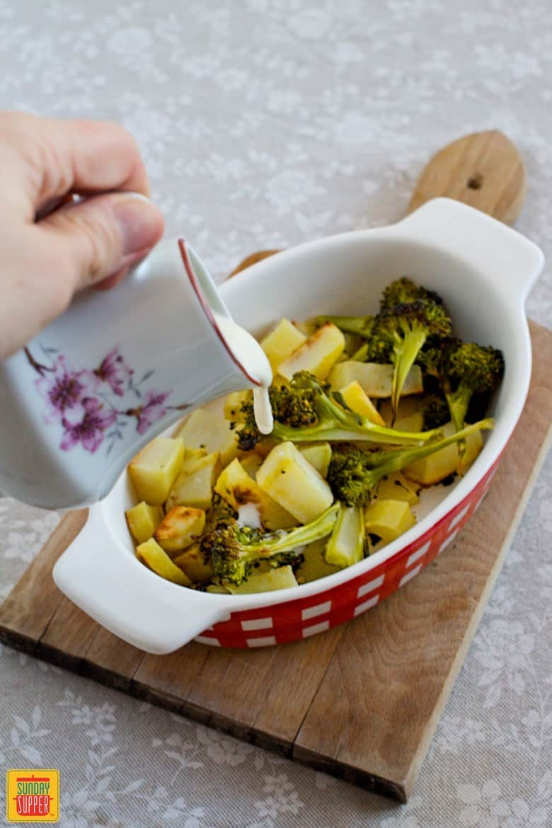 Vegetables with cheese sauce - roasted broccoli and potatoes being covered with cheese sauce