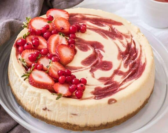 This beautiful Strawberry Swirl Cheesecake is easy to make at home and it's an absolute classic. Homemade strawberry sauce and smooth, creamy baked cheesecake.