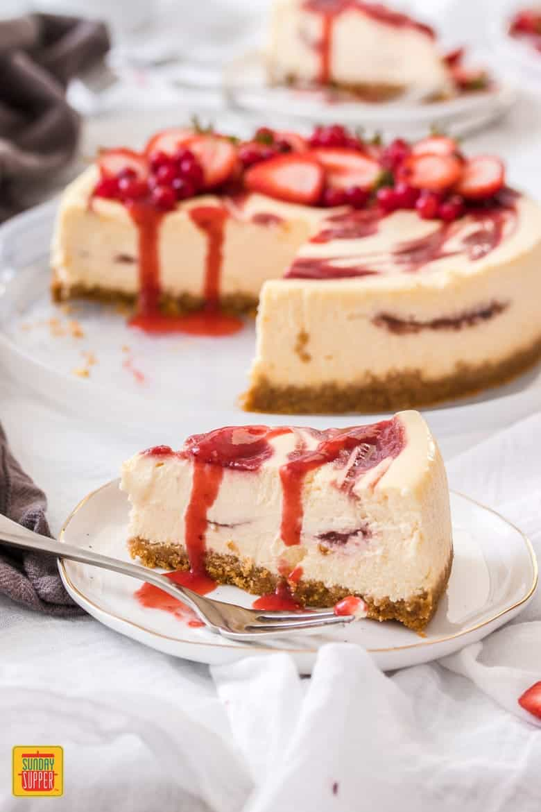 A slice of strawberry swirl cheesecake topped with strawberry sauce