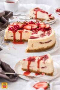 Slice of strawberry swirl cheesecake on a plate in front of the whole strawbery swirl cheesecake on a platter